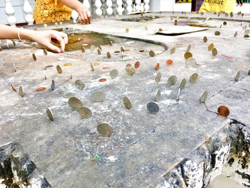 Антиквариат Таиланда виска пожертвования золотой буддийский дарит перемещение Будду веры руки объекта монетка бата следа ноги вер стоковая фотография