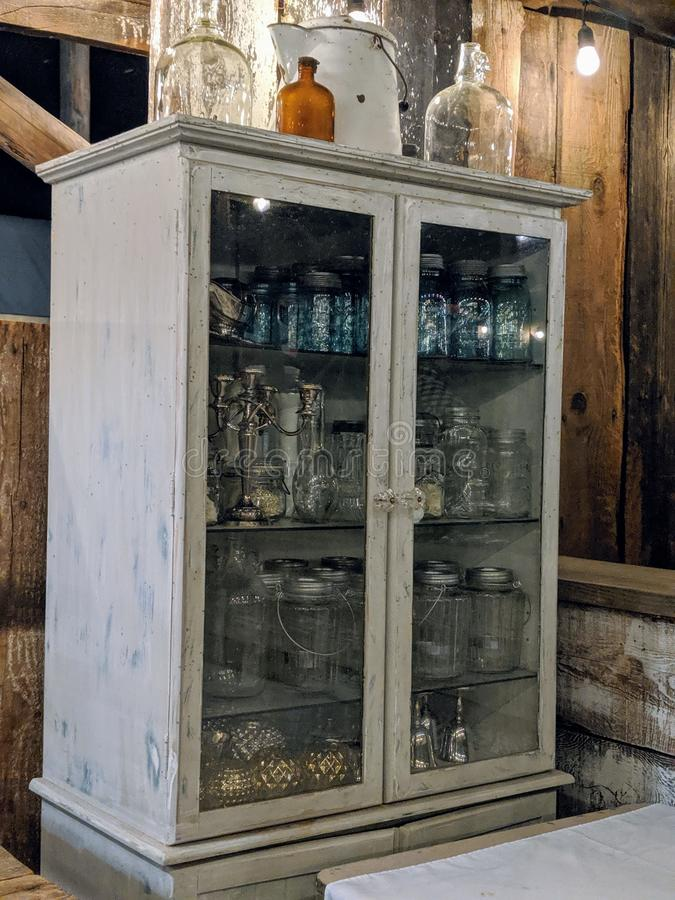 Антикварный деревянный шкаф С Стеклянными Дверями, Заполненными Старыми Машками И Бутылками В Барне стоковое фото