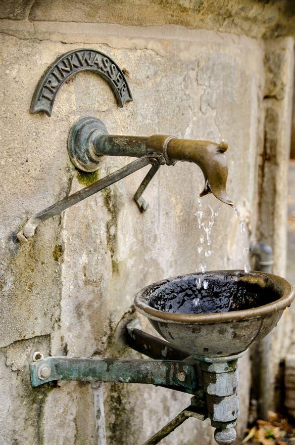 Антикварный фонтан, пьющий медь, на улице в городе Наумбург, Германия стоковое фото
