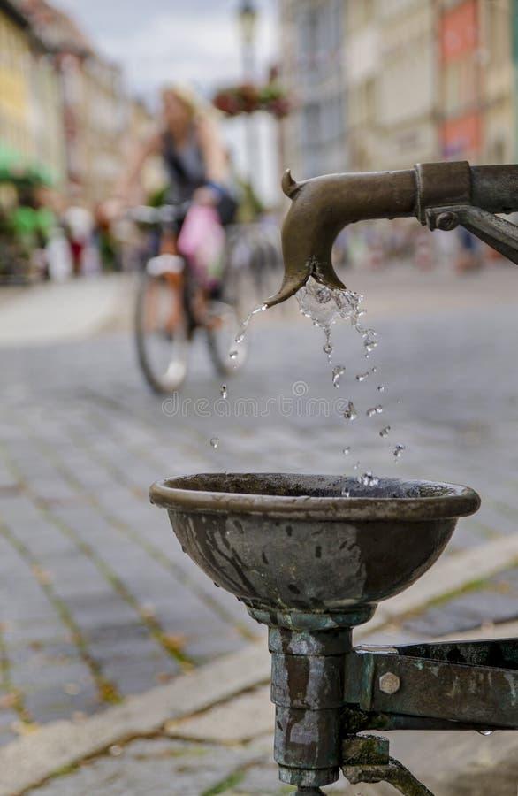 Антикварный фонтан, пьющий медь, на улице в городе Наумбург, Германия стоковые изображения