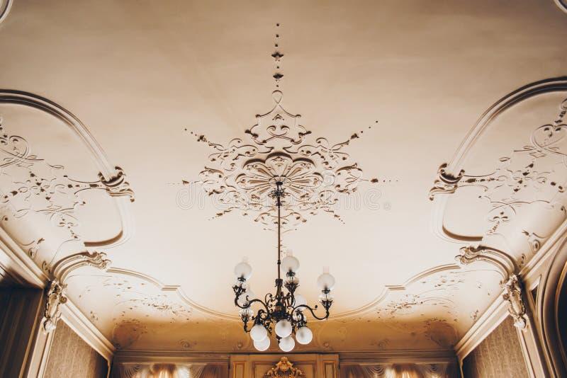Античная дизайнерская люстра на потолке со штукатуркой и картины в роскошном конце-вверх особняка стоковая фотография rf