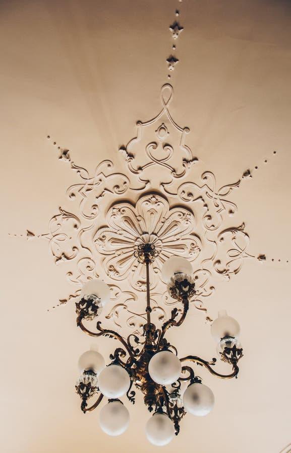Античная дизайнерская люстра на потолке со штукатуркой и картины в роскошном конце-вверх особняка стоковые изображения rf