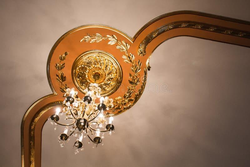 Античная дизайнерская люстра на потолке со штукатуркой и картины в роскошном конце-вверх особняка стоковое изображение