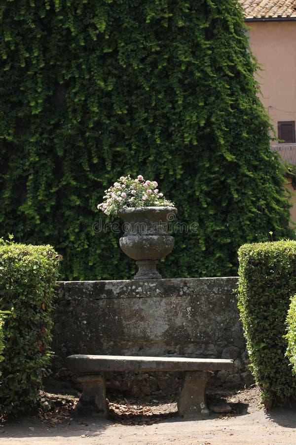 Античная каменная ваза с цветками в саде стоковая фотография rf