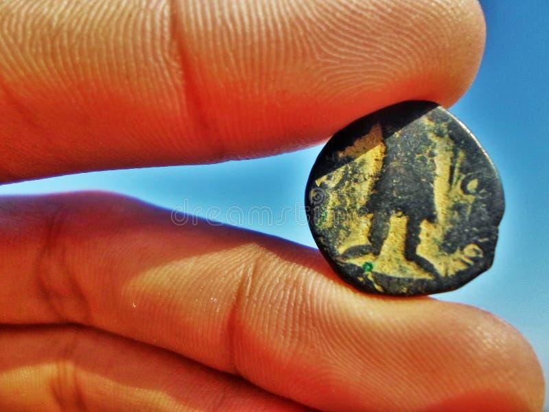 Античная каменная монетка между пальцами на сини стоковая фотография
