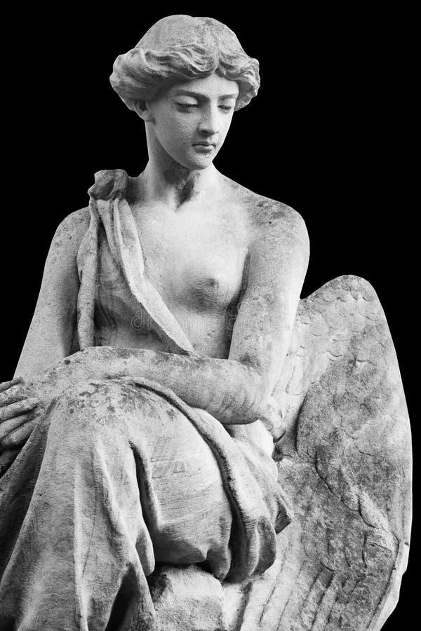 Античная каменная статуя ангела изолированная на черной предпосылке стоковое фото rf