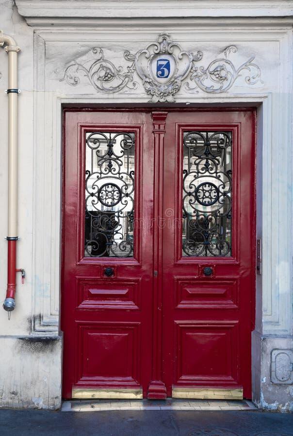 Античная красная дверь с обрамленными деревянными панелями и богато украшенные решетки на окнах двери старого здания в Париже Фра стоковые изображения rf