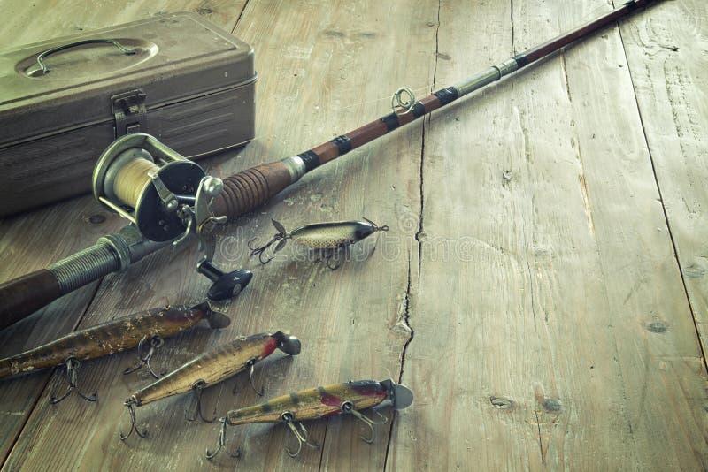 Античная рыболовная удочка и прикормы на поверхности древесины Grunge стоковые изображения rf