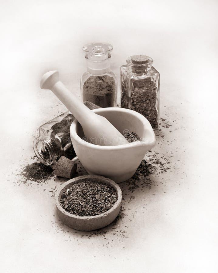 Античные миномет и пестик тона sepia со специями и травами на брезентовой парусине стоковые фото