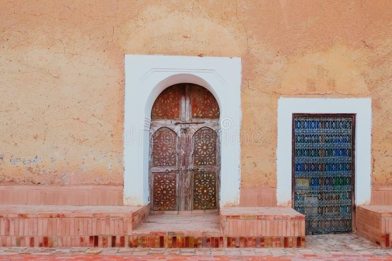 Античные морокканские двери против старой оранжевой розовой стены стоковая фотография