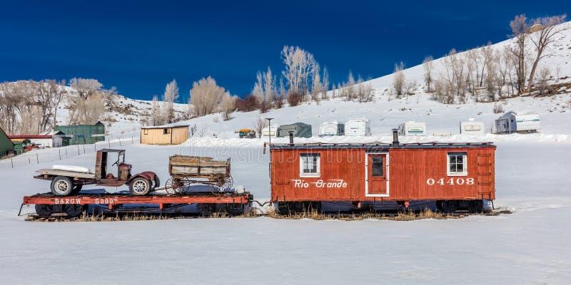 Античный красный автомобиль rarilroad и старые тележка и фура в середине снежного поля в центральном Колорадо в зиме стоковые фотографии rf