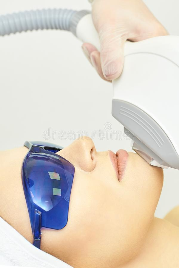 Анти- процедура удаления угорь Прибор косметологии Клиника женщины лицевая затягивая Красивые девушка и рука доктора стоковое фото