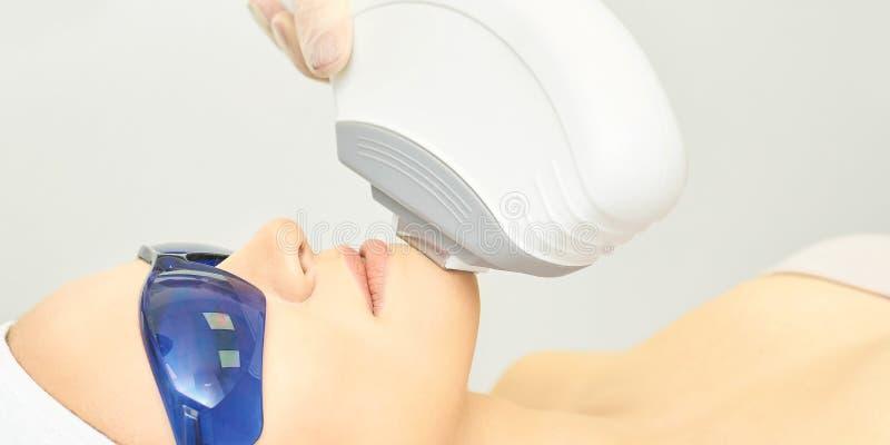 Анти- процедура удаления угорь Прибор косметологии Клиника женщины лицевая затягивая Красивые девушка и рука доктора стоковое изображение rf