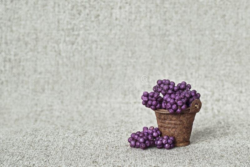 Апатичные ягоды в ржавом ведре на предпосылке холста - натюрморта в загородном стиле стоковые изображения