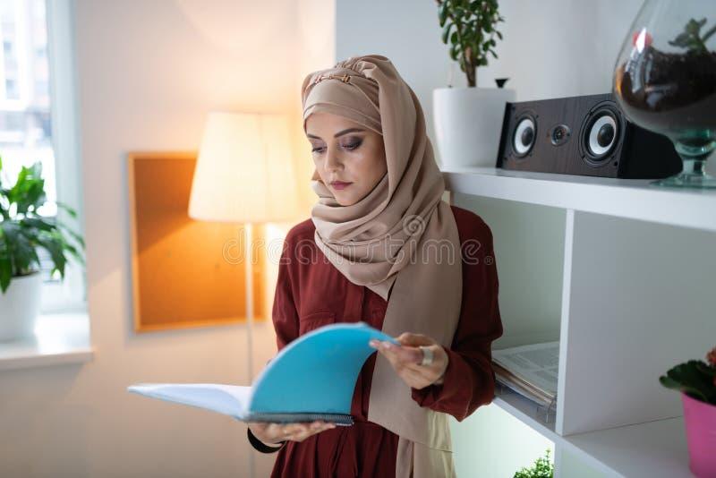 Апеллировать головной платок учителя нося читая некоторые газеты стоковая фотография