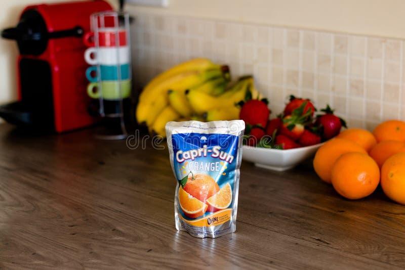 апельсиновый сок Капри-солнца na górze деревянного стола с здоровым плодоовощ на заднем плане стоковое фото rf
