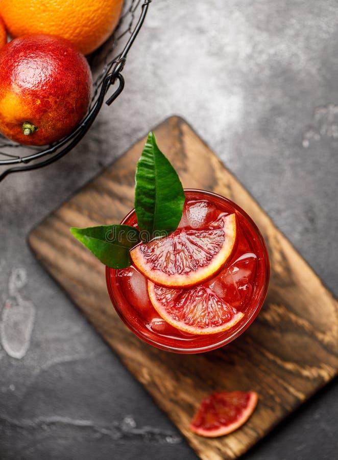 Апельсиновый сок крови с льдом и оранжевый кусок Свежий коктейль лета с красными апельсинами в стекле коктеил свежий Безалкогольн стоковая фотография