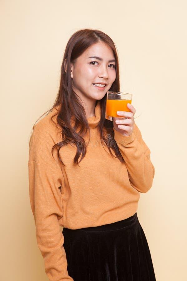 Апельсиновый сок молодого азиатского питья женщины стоковое фото rf