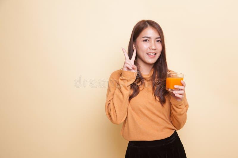 Апельсиновый сок молодого азиатского питья знака победы выставки женщины стоковое фото rf