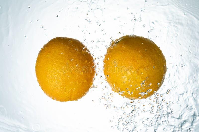 Апельсины мочат выплеск стоковое изображение