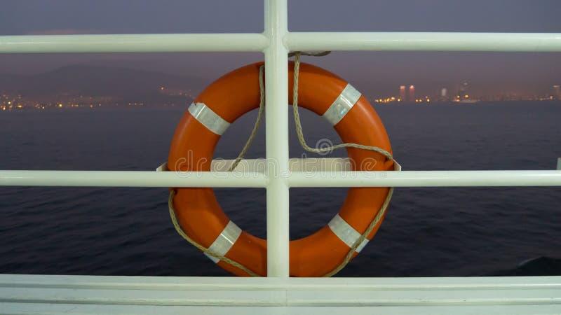 Апельсин lifebuoy на перилах палубы туристического судна на сумраке стоковые изображения