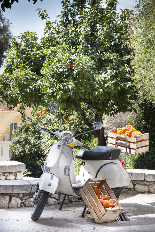 Апельсины в коробке Старый итальянский мотоцикл Зеленые оранжевые деревья на заднем плане стоковое фото rf