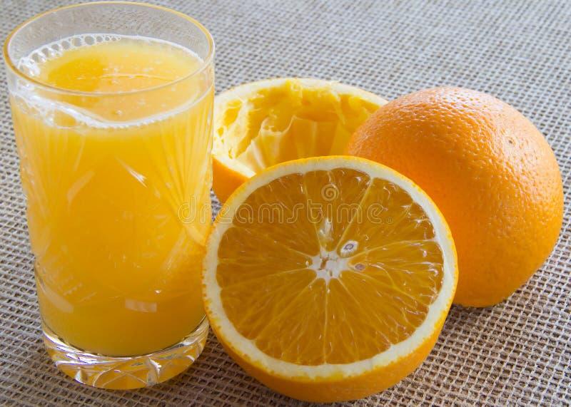 Апельсины и стекло сока на таблице стоковые изображения