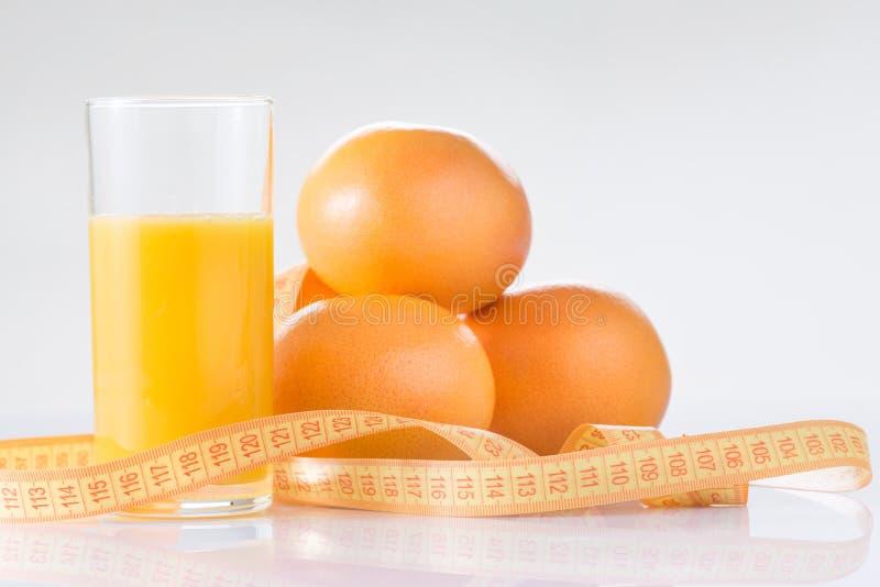 Апельсины, свежий сок и измеряя лента стоковое изображение