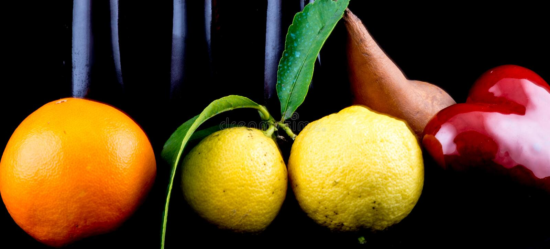 Апельсин, лимон и груша на черной предпосылке стоковая фотография rf