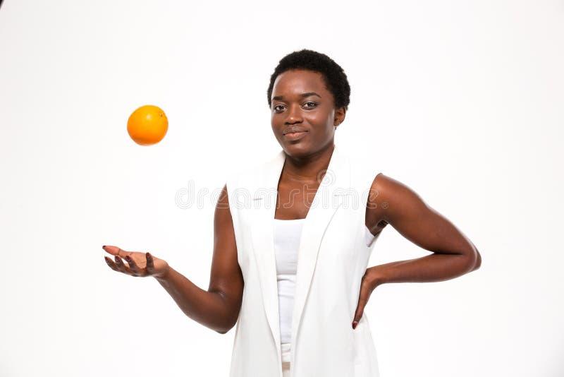 Апельсин счастливой шаловливой африканской женщины thowing вверх в воздухе стоковое фото rf