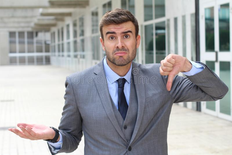Апологетический давать бизнесмена большие пальцы руки вниз стоковое изображение rf