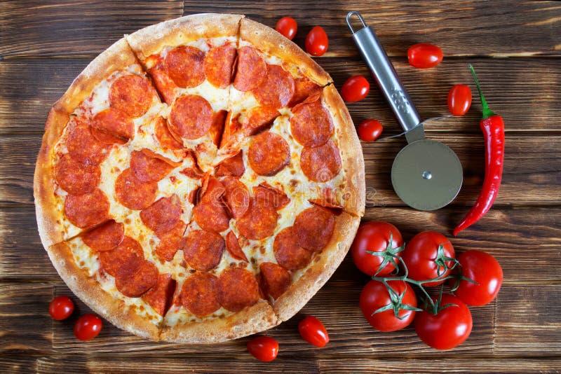 Аппетитная пицца с pepperoni и лож салями на деревянной поверхности рядом с красивыми томатами и красным перцем   стоковое фото rf