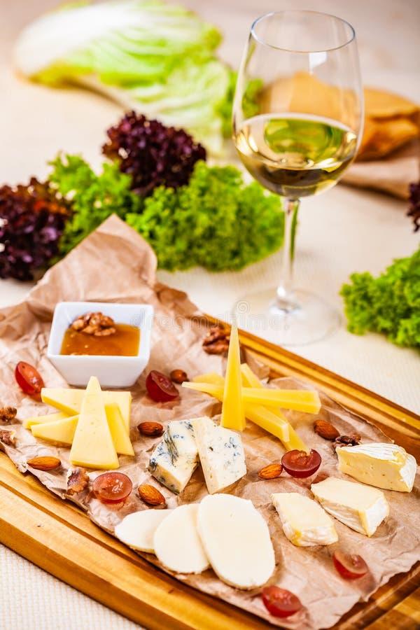 аппетитно Блюдо сыров с медом, гайками и виноградиной стоковое изображение
