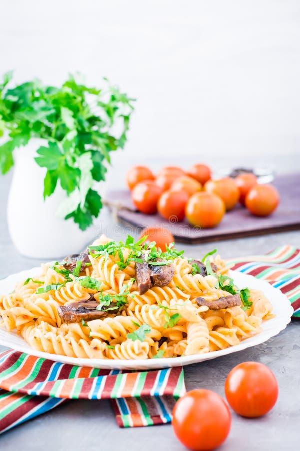 Аппетитные макаронные изделия с зажаренными грибами и свежими травами на плите стоковые изображения