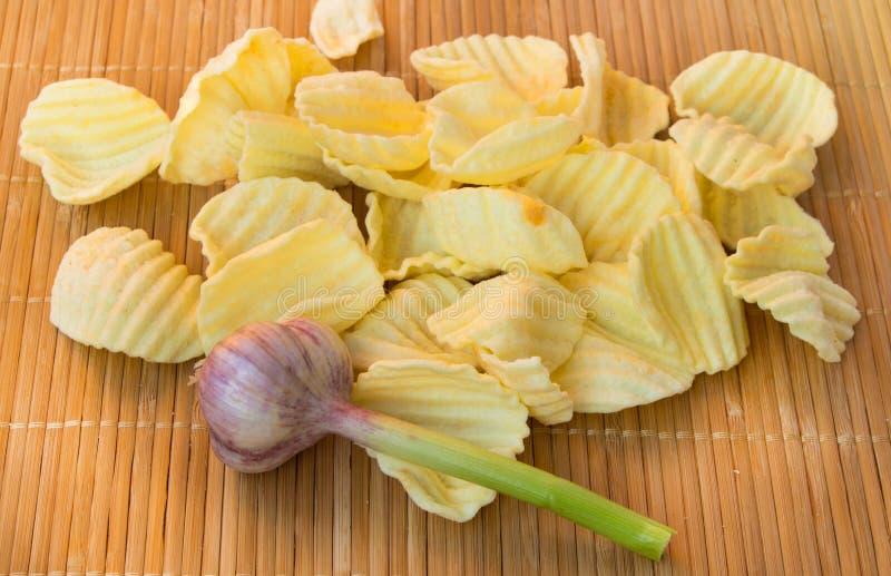 Аппетитные хрустящие картофельные чипсы на сплетенной бамбуковой еде салфетки, нездоровых или неправильных, но очень вкусный стоковая фотография rf