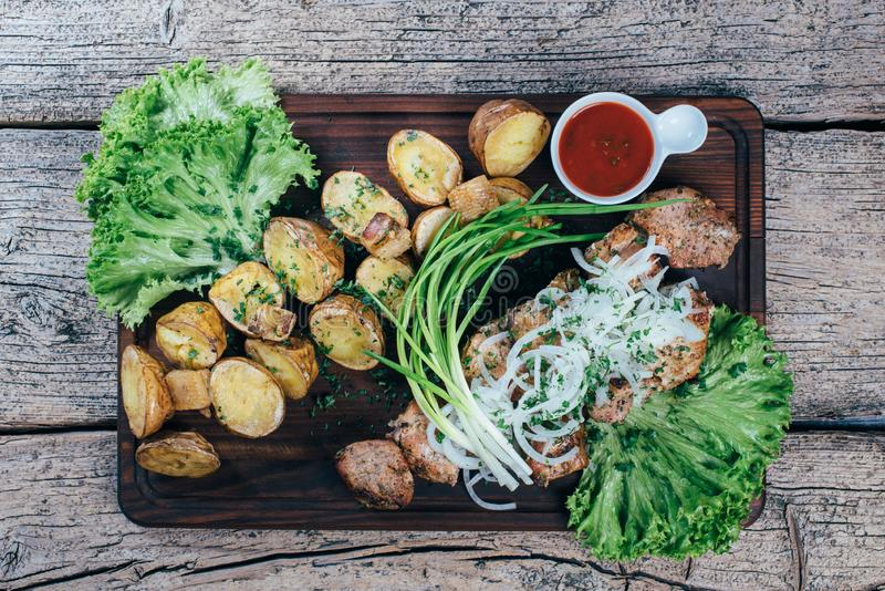 Аппетитные части зажаренной в духовке свинины на гриле, представленном на деревянной доске, вместе с листьями зеленого салата и к стоковые фотографии rf