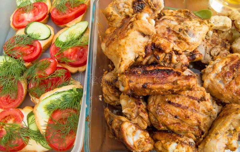 Аппетитные части зажаренных цыпленка и тоста с томатами и огурцами, очень вкусной едой пикника, солнечным светом, лучами, предпос стоковое фото rf