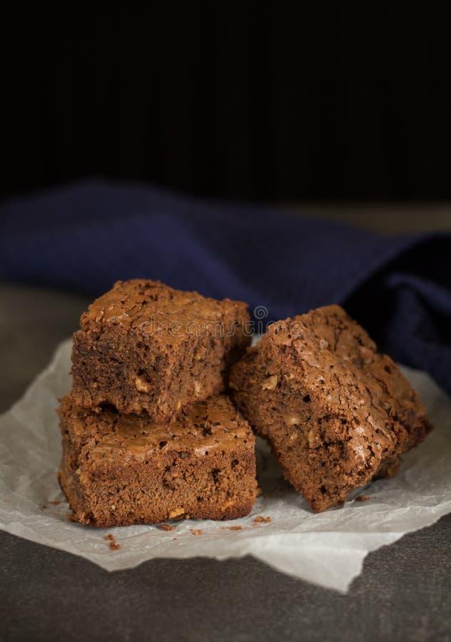 Аппетитные части шоколадного торта на пергаменте на темноте стоковая фотография rf