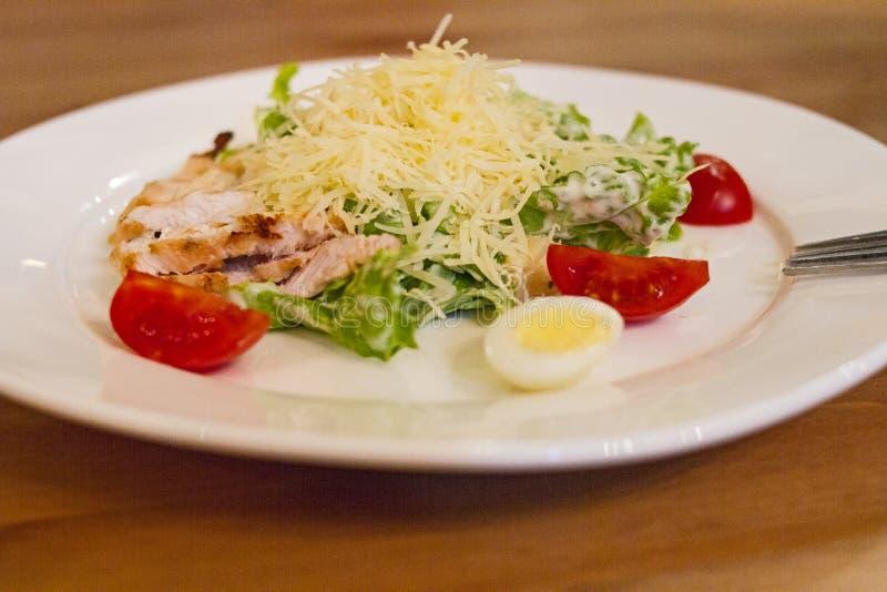 Аппетитный салат цезаря с цыпленком на гриле, томат вишни, сыр, яичко триперсток и салат листают на белой плите стоковая фотография rf