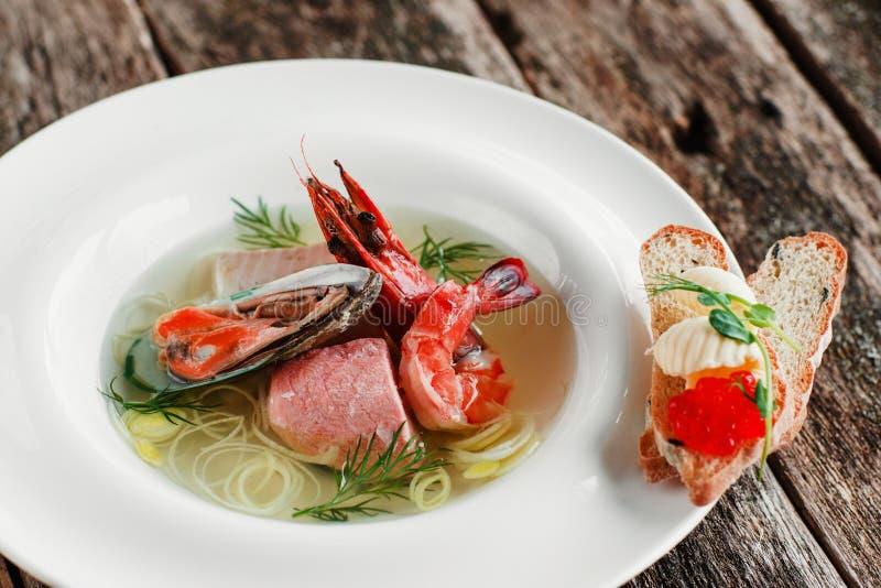 Аппетитный суп морепродуктов с канапе икры стоковые изображения
