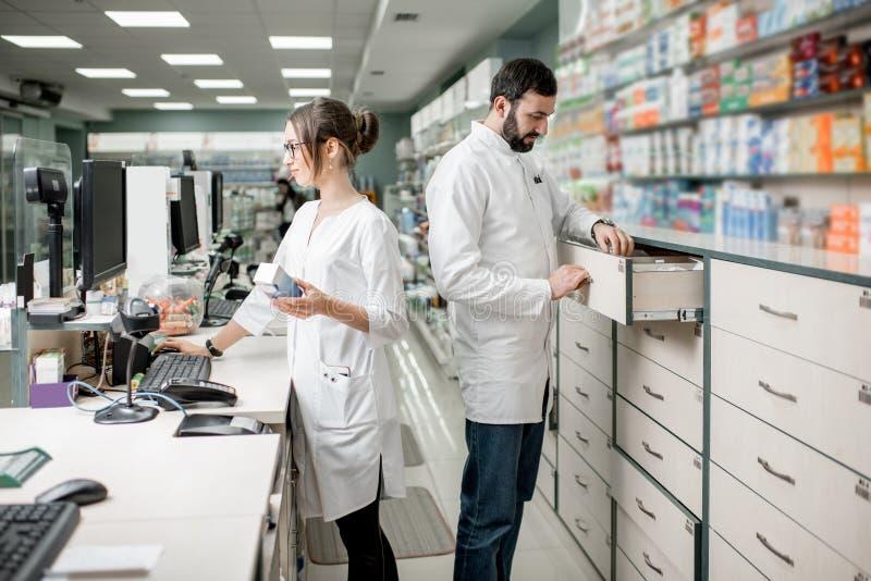 Аптекари работая в магазине фармации стоковое фото
