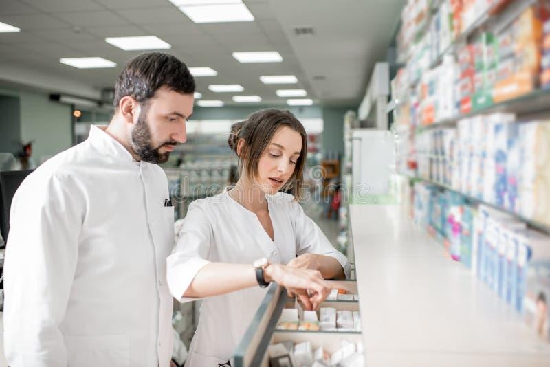 Аптекари работая в магазине фармации стоковые фото