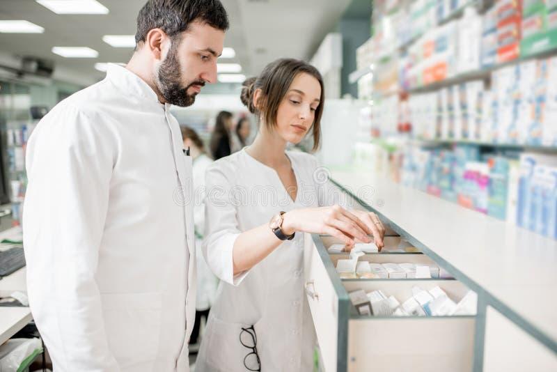 Аптекари работая в магазине фармации стоковые фотографии rf