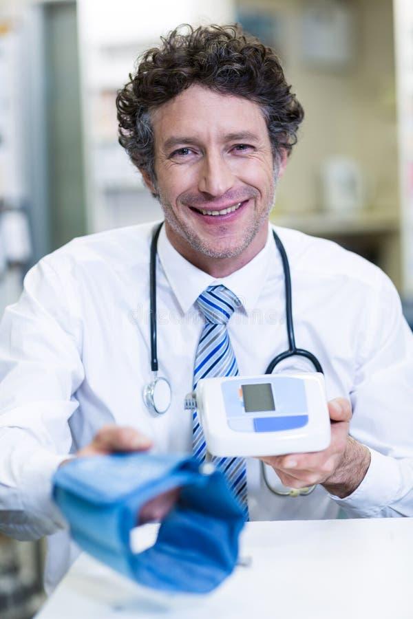 Аптекарь держа монитор кровяного давления в фармации стоковые фотографии rf
