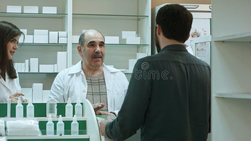 Аптекарь и клиент имеют конфликт и пробуют разрешить проблему на фармации стоковое фото rf