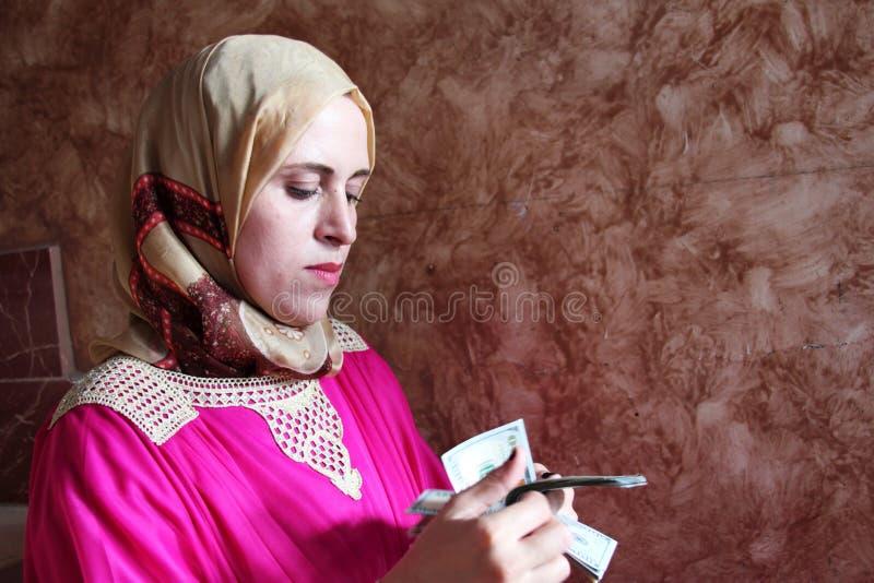 Арабская мусульманская женщина подсчитывая деньги стоковая фотография rf