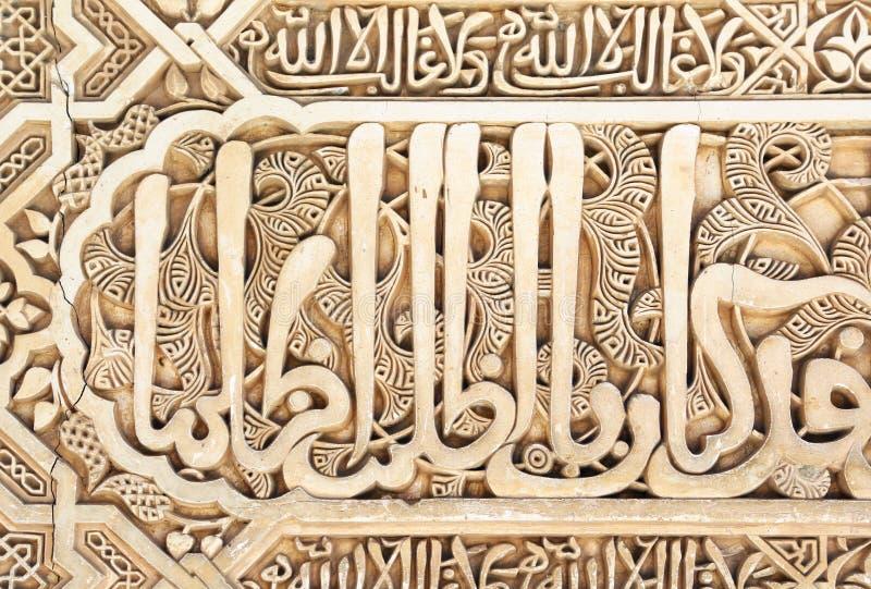 Арабские слова высекаенные в Альгамбра, Гранаде стоковое фото rf