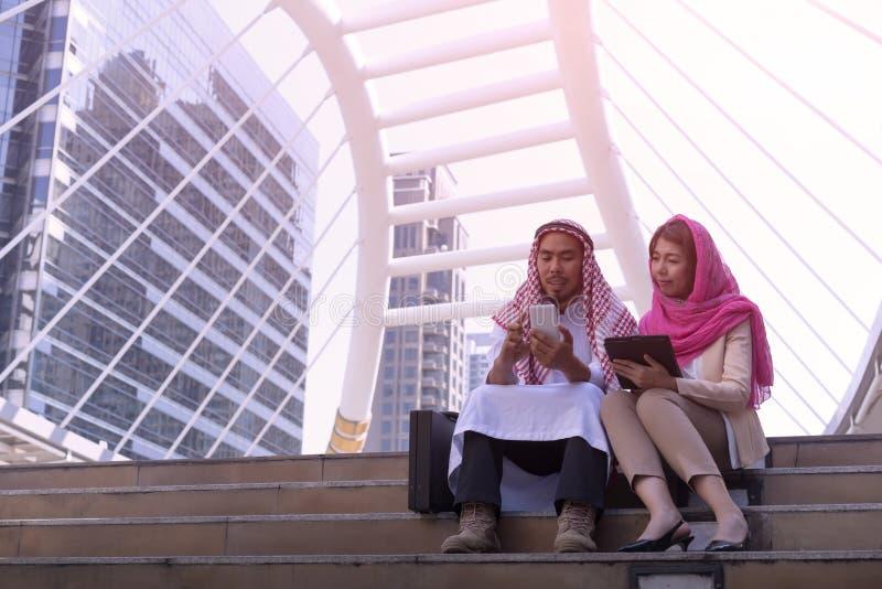 Арабский бизнесмен и коммерсантка араба усаживание говорят, используют mobi стоковая фотография
