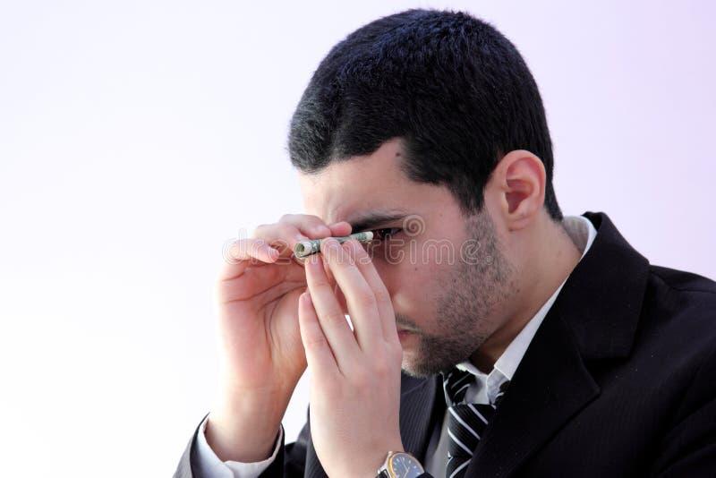 Арабский бизнесмен смотря через деньги стоковые изображения