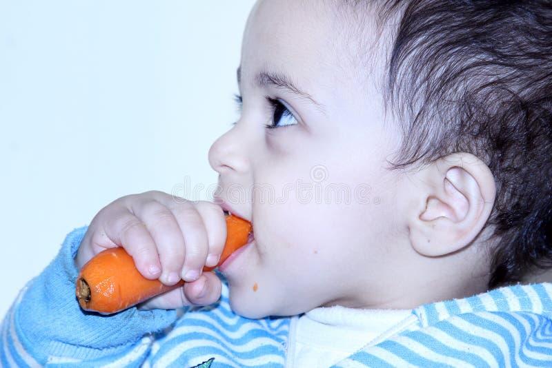 Арабский египетский ребёнок есть морковь стоковое фото